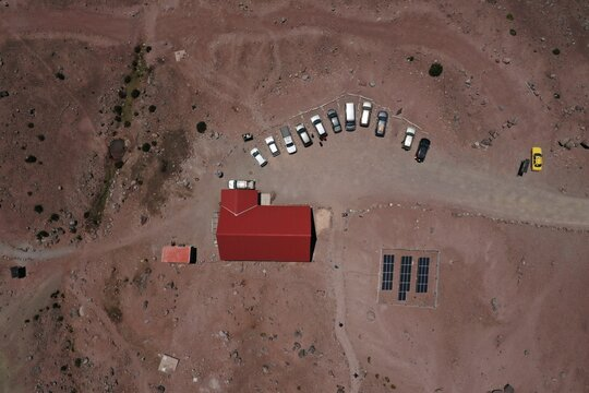 Aerial view showing a house with a red tiled roof with many cars parked in front of it and a small area with solar panels next to it
