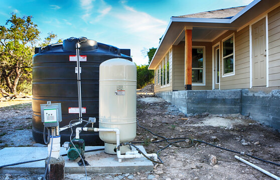 Deep water well set up in front of home construction.  Drilled draw well with pressure switch and storage tank.