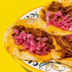 Mexican cochinita pibil tacos with onion on yellow background