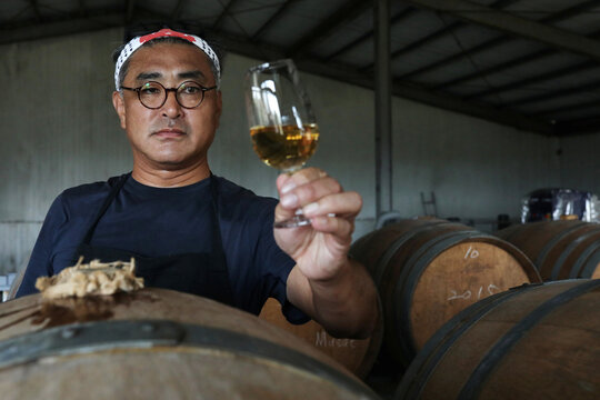 Chen Chien-hao, 52, holds a glass of his wine at Shu Sheng Leisure Domaine in Taichung