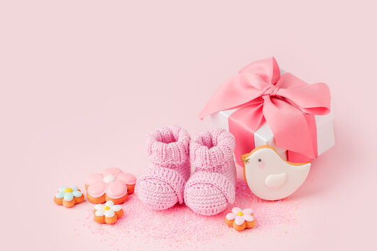 Pair of small pink baby socks, cookies, gift box on pink background with copy space for your warm message, baby shower, first newborn party background, copy space, monochrome