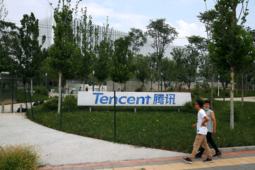 People walk past an office building of Chinese tech firm Tencent, owner of messaging app WeChat, in Beijing