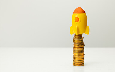 Rocket and stack of gold coins on gray background