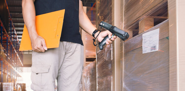 Worker scanning bar code scanner with label of goods. Computer equipment for warehouse inventory management.
