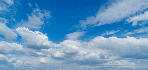 Contrasting expressive clouds against the blue sky as a backdrop.