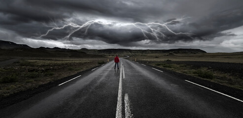 Man on the road with storm and lightning