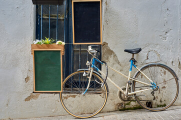 Two empty bulletin boards hanging on a wall next to an old bicycle leaning against a white wall with a window