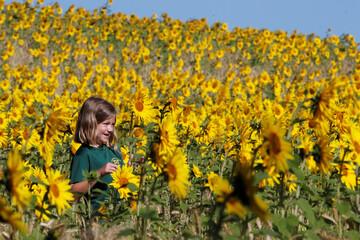 A child walks in a field of sunflowers, amid the coronavirus disease (COVID-19) outbreak, in Chorleywood
