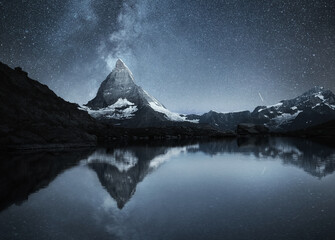 Swiss landscape. Matterhorn and reflection on the water surface at the night time. Milky way above Matterhorn, Switzerland. Travel image.