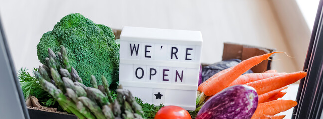 Text We're open and Fresh green and vegetables box