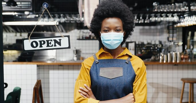 Portrait of beautiful African American young woman waitress in apron and medical looking to camera with table open at cafe entrance outdoor. Pretty barrista standing at bar door with board open Reopen