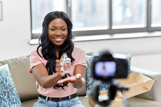 blogging, videoblog and people concept - happy smiling african american female beauty blogger with camera and perfume videoblogging at home