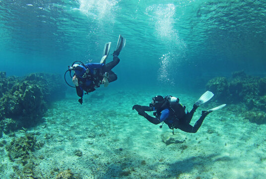 Diving instructor and student in underwater exercise. Instructor teaches student to dive. Underwater scuba diving education and training.