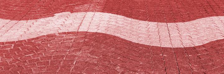 Wavy light and dark red cobblestone pavement on the street. Panoramic image