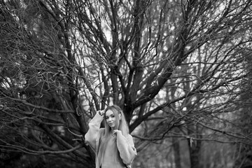 Monochrome portrait of young attractive girl with long hair wearing sweater posing on background of autumn forest.