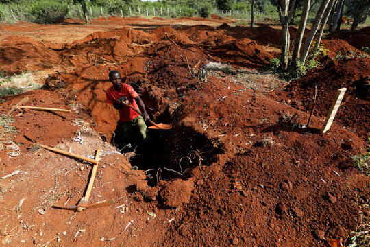 A grave digger uses a shovel to adjust the size of a newly dug grave at the separated section of the muslim cemetery, in Nairobi