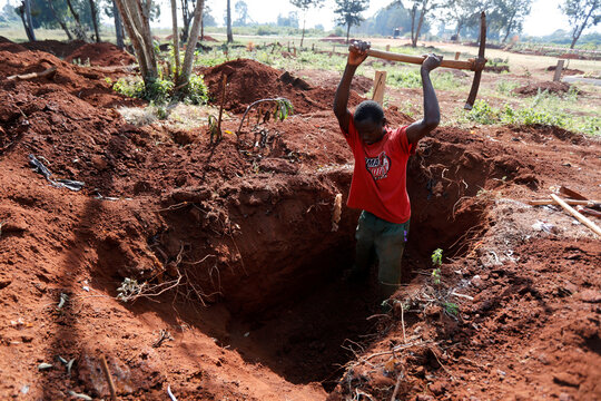 A grave digger uses a pickaxe to adjust the size of a newly dug grave at the separated section of the muslim cemetery, in Nairobi
