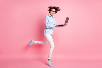Full length body size profile side view of her she nice attractive skinny cheerful brown-haired girl jumping running study learn use laptop web conference isolated pink pastel color background Wall mural