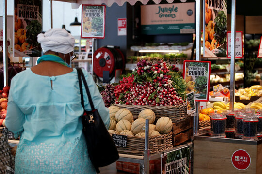 A customer shops for vegetables at a Monoprix supermarket operated by Casino Group, in Paris