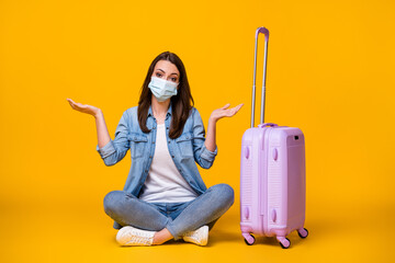 Oops. Full body photo of pretty young lady sitting floor unhappy missed flight rolling bag travel airport quarantine wear facial mask casual denim shirt shoes isolated yellow color background