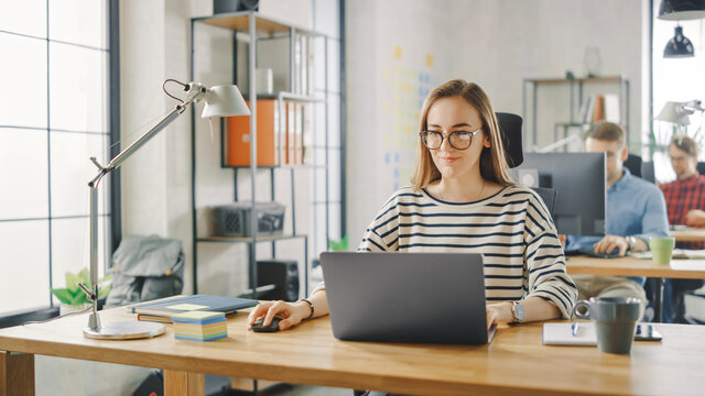 Beautiful Young Woman in Glasses is Working on a Laptop in a Creative Business Agency. They Work in Loft Office. Diverse People Working in the Background. She's in a Good Friendly Mood.
