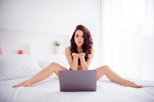Photo of naughty hot beautiful lady home work quarantine online laptop chat send air kisses screen ready start show spread legs sides wear lace bikini sitting white linen sheets indoors
