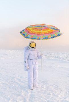 Astronaut standing with umbrella
