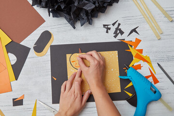 The girl creates a handcrafted pumpkins from colored paper on a wooden background for invitation cards of Halloween party. Flat lay