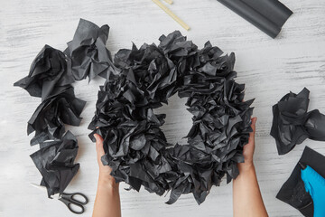 Female hands hold handcrafred holiday wreath for decoration interior from black paper tyshyu on a wooden background. Flat lay