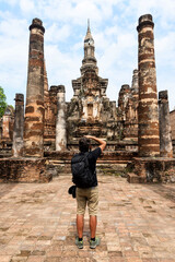 Foto op Canvas Historisch mon. Man taking pictures of an ancient Buddhist temple in Sukhothai, Thailand