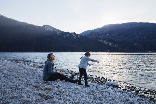 Pregnant mom looks amused at her daughter playing with pebbles by the lake