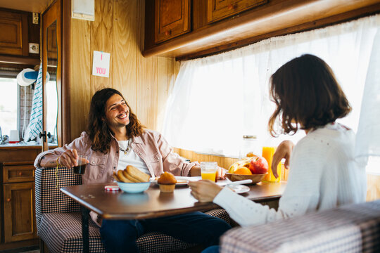 nice young couple having breakfast in a vintage motor home