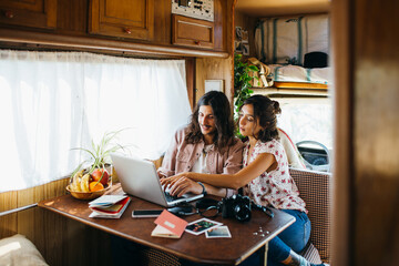 nice young couple watching pictures in a laptop in a sunny motor home