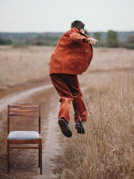 Anonymous woman in suit jumpingÔøΩinÔøΩrural field