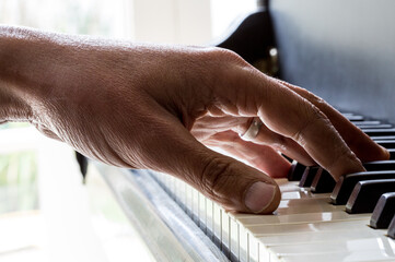 A male hand resting on a piano keyboard