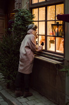 The girl looks in the decorated Christmas window