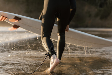 surfer in wetsuit picking up surfboard out of water at sunset