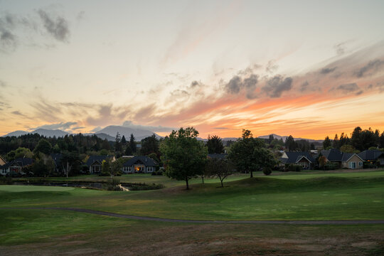An Oregon sunset at a green golf course with mountains in the distance