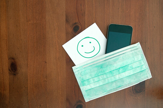 healthcare_hygienic mask_smartphone_smile_paper_wooden background