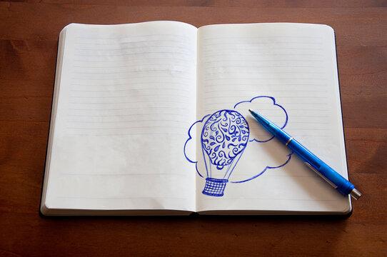 Doodle_hot-air balloon_paper notebook_pen_wooden background