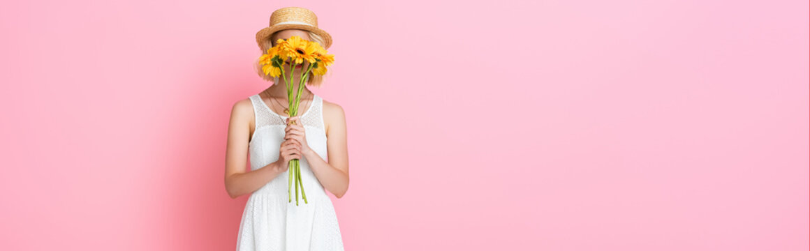 website header of young woman in straw hat and white dress covering face with yellow flowers on pink