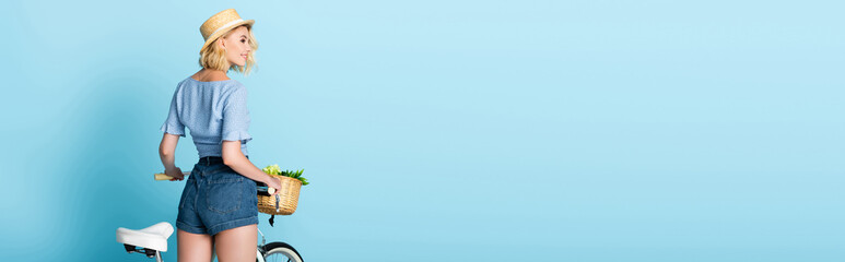 panoramic concept of woman in shorts standing near bike on blue