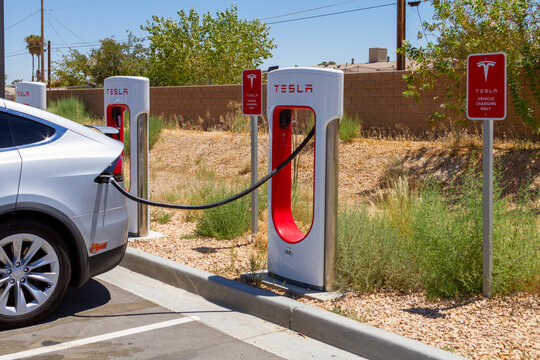 Yermo, CA / USA – August 1, 2020: A car is attached to a Tesla vehicle charging station located between Los Angeles and Las Vegas off of Interstate 15 in Yermo, California.