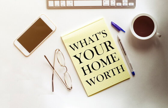 What s is Your Home Worth text on the yellow paper with phone, coffee, pen
