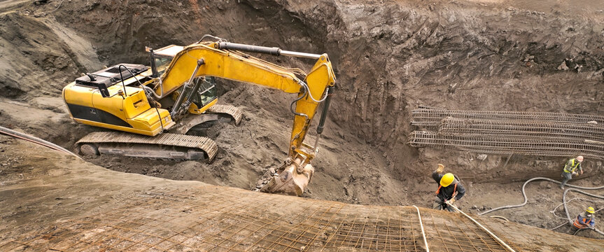 Panoramic view of an excavator vehicle in construction site among an abseil worker. Excavation site where deep construction foundations will be made.