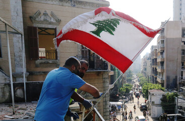 Men attach the Lebanese flag on a building following Tuesday's blast in Beirut's port area