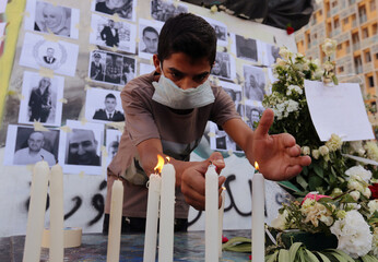 A man lights a candle to mourn the victims of Tuesday's blast in Beirut's port area, at Martyrs' Square in Beirut