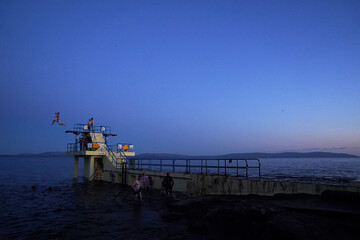 A man jumps off Salthill beach diving boards during sunset in Galway