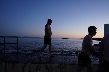 Swimmers walk during sunset in Galway