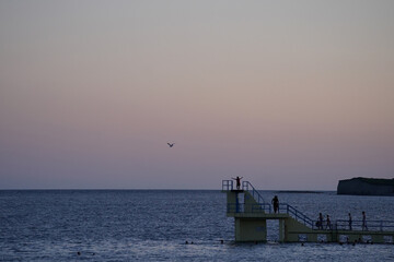 A person stands on Salthill beach diving boards during sunset in Galway